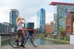 Dusseldorf Tyskland - September 14, 2014: tar unga kvinnor med citybike fotoet av byggnader i massmediahamn Royaltyfria Bilder