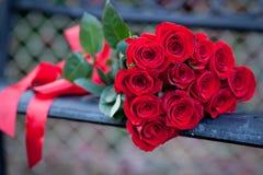 Dussin röda rosor på en bänk Royaltyfria Bilder