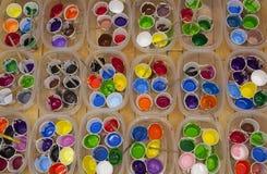 Dussintals väl använda målarfärgkoppar och målarpenslar med vividly sänkan Arkivbilder