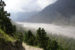 Dust blows up the valley. River, Mountains and Forest, with dust blowing up the valley. Nepal Himalayan scene taken whilst trekking around the Annurpurna Circuit Stock Photography