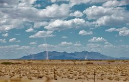 Dust Devils in the New Mexico Desert. Two dust devils draw the desert sand upward as their rotating winds travel across the desert in southern New Mexico Stock Image