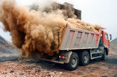 Dust explosion when loading red truck at the mine Stock Photos
