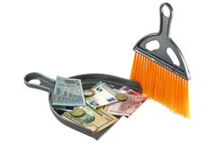 A dust pan with Euro and US Dollar in it. An orange dust brush next to a dust pan with Euro and US Dollar in it royalty free stock images
