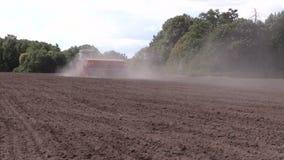 Dust rise from tractor fertilize prepare soil in field stock video
