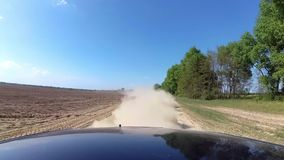 Dust rising from automobile wheels automobile driving on rural gravel road. stock footage