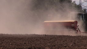Dust rising from tractor fertilizer prepare soil in field stock video