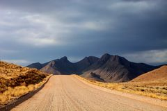 The dust road in the mountainous landscape of central Namibia Royalty Free Stock Photography