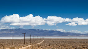 Dust road with power poles aside Stock Images