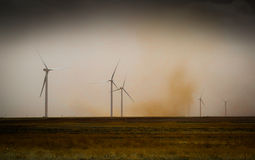 Dust Storm passes by wind turbines. A dust storm passes several wind turbines in Texas. This shows the growth of of higher eco friendly energy solutions here in Stock Photos