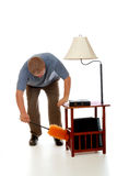 Duster Man. Man dusting a side table with lamp using a fluffy orange duster. Isolated on white stock photography