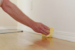 Dusting a Baseboard. Male caucasian hand and arm seen wiping a folded yellow rag along the lower white wall trim near the wood floor to remove dust Royalty Free Stock Images