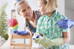 Dusting and cleaning. Happy family dusting and cleaning at home together stock image