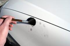 Dusting for fingerprints. Using fingerprint powder on a vehicle to locate latent fingerprints stock images