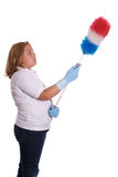 Dusting Girl. A young girl using a long duster to clean with, isolated against a white background Royalty Free Stock Image