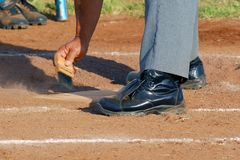 Dusting Home Plate. A baseball umpire dusts home plate Royalty Free Stock Photo