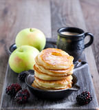 Dusting with icing sugar over apple fritters Stock Photos