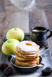 Dusting with icing sugar over apple fritters Stock Photo