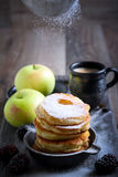 Dusting with icing sugar over apple fritters Royalty Free Stock Image