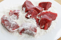 Dusting meat cubes Royalty Free Stock Images