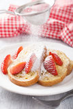 Dusting powder sugar over french toast with berry. Dusting powder sugar over french toasts with strawberry royalty free stock image