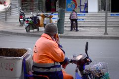 A dustman with an orange suit on the motorcycle. Kunming, Yunnan, China Stock Photography