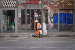 A dustman with an orange suit on the street. Kunming, Yunnan, China Royalty Free Stock Image
