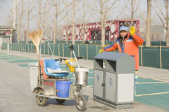 A dustmen. A dustman is cleaning the dustpan happily by a sightseeing square, China Royalty Free Stock Photography