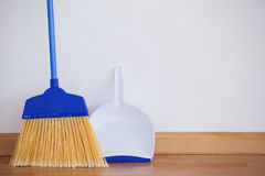 Dustpan and sweeping broom leaning against white wall Stock Photo