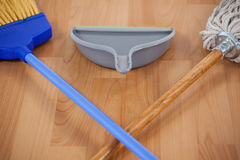 Dustpan, sweeping broom and mop on wooden floor Royalty Free Stock Photography
