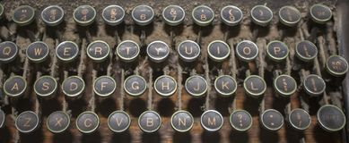 A dusty antique QWERTY typewriter keyboard. With black keys and brass rims stock photos