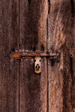 Dusty bolt on grungy old wooden door. Royalty Free Stock Image