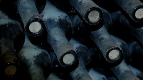 Dusty Bottles Of Wine Lie On Top Of Each Other In The Wine Cellar. Dusty and old wine bottles lie in a dark wine cellar stock video