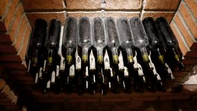 Dusty Bottles Of Wine Lie On Top Of Each Other In The Wine Cellar. Dusty and old wine bottles lie in a dark wine cellar stock video footage