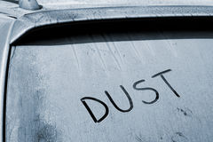 Dusty rear car windshield with word Dust written Stock Photos