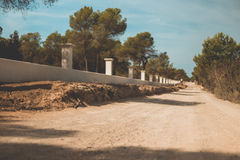 Dusty deserted Spanish Dirt road lined by a white wall and green trees Stock Photography