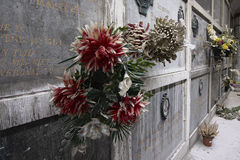 Dusty fake flowers on old grave stones Stock Photo