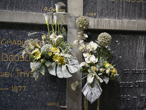 Dusty fake flowers on old grave stones Royalty Free Stock Photo