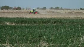 Dusty field being plowed by a green tractor. A wide still shot of a green tractor plowing a dusty field in Uzbekistan, with green grass in the foreground stock video