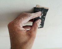 Dusty hand holdinng sandpaper Royalty Free Stock Photography