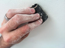 Dusty hand sanding a white surface Royalty Free Stock Photography