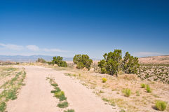 Dusty high desert road. A view along a hot, desolate and dusty high desert road in Northern New Mexico, USA royalty free stock images