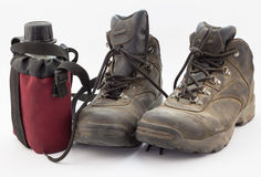 Dusty hiking boots and red water bottle on white Royalty Free Stock Photos
