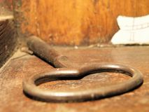 Dusty key on wooden surface Stock Image