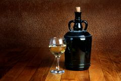 Dusty old bottle and glass of white wine Royalty Free Stock Images