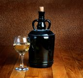 Dusty old bottle and glass of white wine Royalty Free Stock Photo
