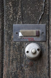 Dusty old doorbell. Detail with dusty old doorbell and empty label on a background with peeling paint and decaying wooden planks royalty free stock photography
