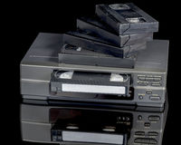 Dusty old VCR with takes and reflection. Antique VCR player with original tapes Stock Photo