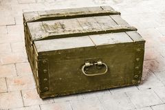 Dusty old wooden box. Standing on the floor tiles Royalty Free Stock Photos