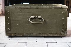 Dusty old wooden box. Standing on the floor tiles Royalty Free Stock Image