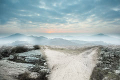 Dusty path leading to mountains Stock Photo